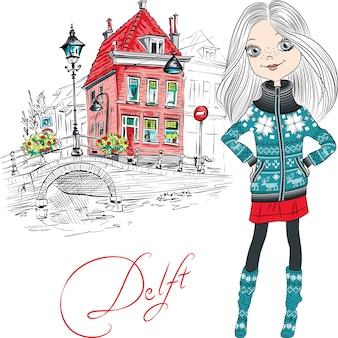 デルフト、オランダ、オランダの伝統的なオランダの家、橋、街灯の近くのかわいい流行に敏感な女の子。