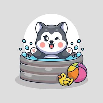 膨脹可能なプールで遊ぶかわいいハスキー犬