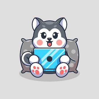 ノートパソコンの漫画を再生するかわいいハスキー犬
