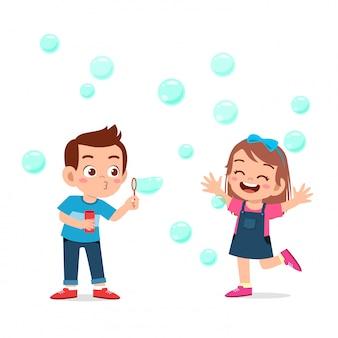 Милый парень мальчик и девочка пускают мыльный пузырь