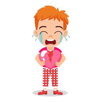 깨진 사랑 심장 모양을 잡고, 울고 서있는 귀여운 꼬마 소년 캐릭터