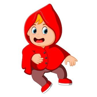 かわいい子供の魔女は赤いマントで歩いている
