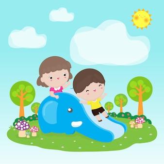 Милые дети веселятся на горке на детской площадке