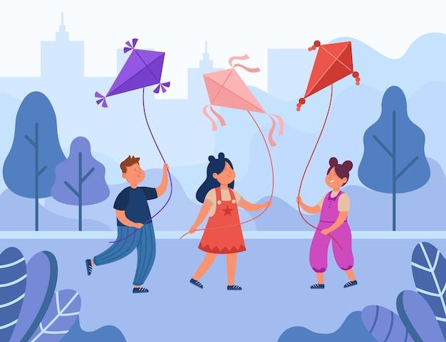公園で凧を持って歩くかわいい子供たち