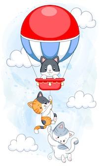 Милые котята висят на воздушном шаре, летящем в небе