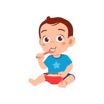 Cute little baby boy eat porridge in bowl with spoon