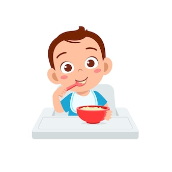 かわいい男の子はスプーンでボウルにお粥を食べる