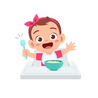 Cute little baby girl eat porridge in bowl with spoon