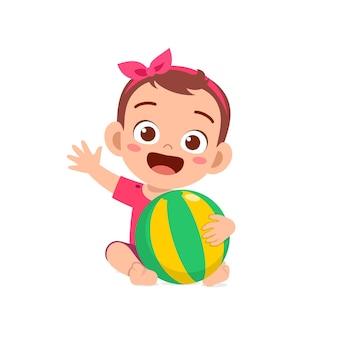큰 공을 가지고 노는 귀여운 아기 소녀