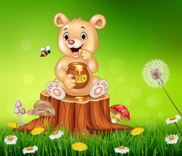 Cute little bear holding honey on tree stump