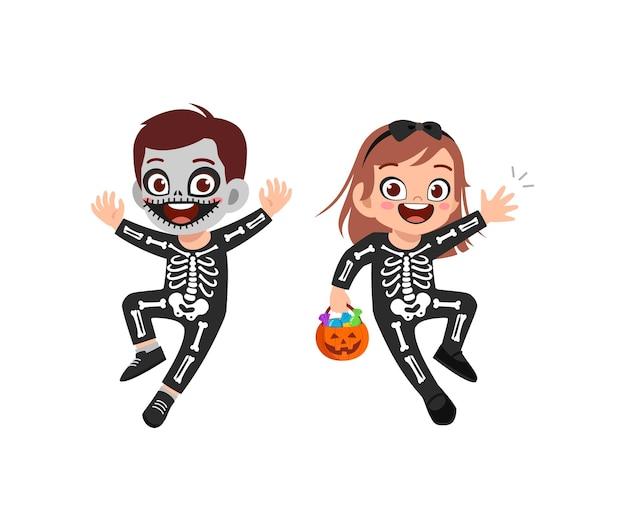 かわいい男の子と女の子がハロウィーンの服のスケルトンコスチュームを祝う