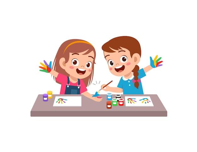 Милый маленький мальчик и девочка, используя краску в руке для искусства