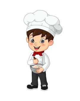 귀여운 소년 요리사는 그릇에 재료를 섞는다