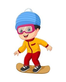 Милый маленький мальчик в зимней одежде играет на сноуборде