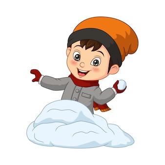 Милый маленький мальчик в зимней одежде, бросая снежок