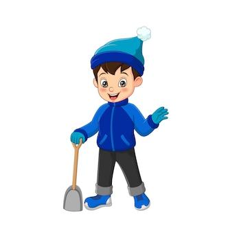 シャベルで冬の服を着たかわいい男の子