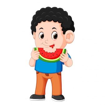 Cute little boy is eating watermelon