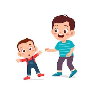 かわいい男の子は一緒に赤ちゃんの兄弟と遊んで、歩くことを学びます