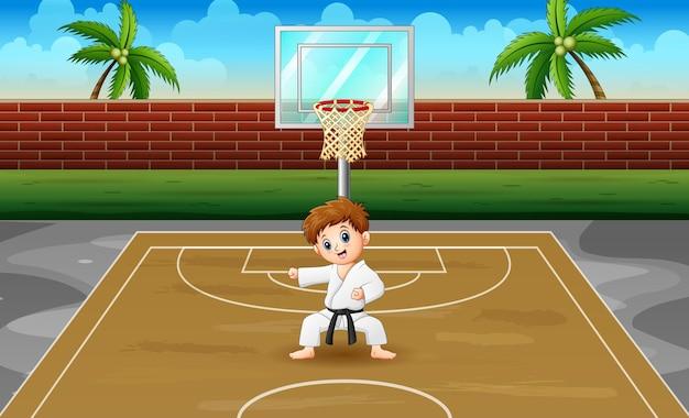 Cute little boy practicing karate in the field