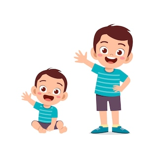 귀여운 어린 소년이 어린 동생과 인사를 합니다.