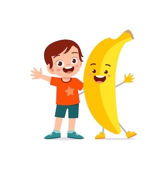 Милый маленький мальчик стоит с персонажем банана