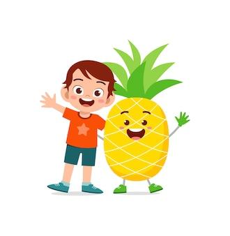 Симпатичный маленький мальчик стоит с персонажем ананаса