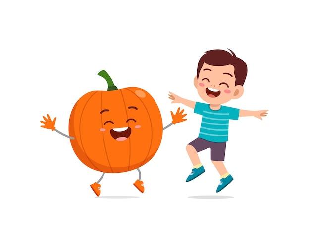 Cute little boy stands with pumpkin character
