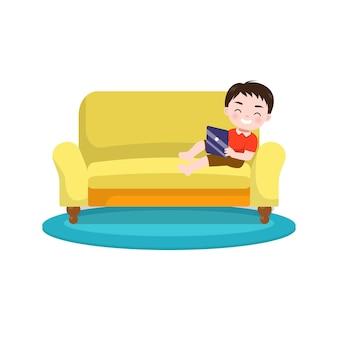 Cute little boy use tablet on sof