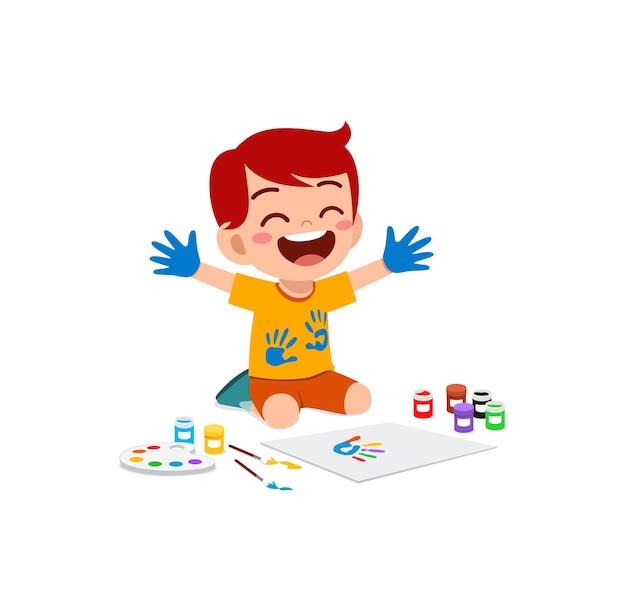 Милый маленький мальчик, используя краску в руке для искусства