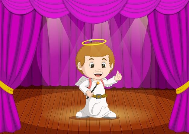 Cute little boy wearing angel costume on stage
