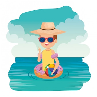 Cute little boy with donut float and beach balloon on the sea