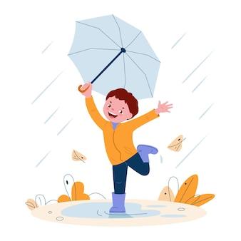 Милый маленький мальчик с зонтиком в резиновых сапогах ветреная погода осенние листья