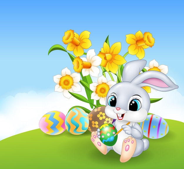 Cute little easter bunny painting an egg