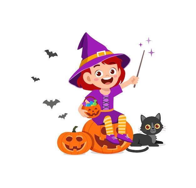 かわいい女の子はハロウィーンの服の魔女の衣装を祝う