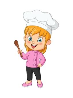 부엌 숟가락을 들고 귀여운 소녀 요리사