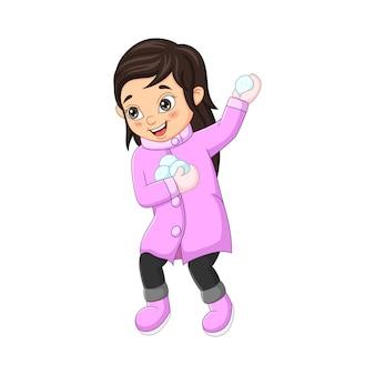 Милая маленькая девочка в зимней одежде, бросая снежок