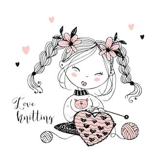 A cute little girl knits a woolen heart on her knitting needles.