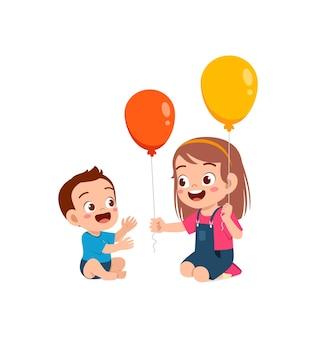 Милая маленькая девочка играет на воздушном шаре с маленьким братом и сестрой