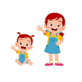 Милая маленькая девочка поздоровается с молодой сестрой