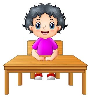 Cute little girl sitting at the desk
