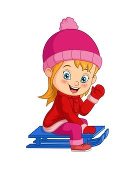 Милая маленькая девочка катается на санках с холма