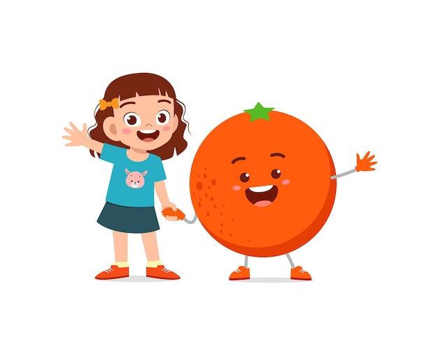 Милая маленькая девочка стоит с оранжевым персонажем