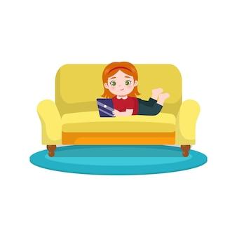 Милая маленькая девочка использует планшет на диване