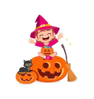 かわいい女の子はハロウィーンの魔女の衣装を着ています