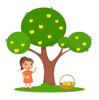 Cute little girl with an apple and a basket full of apples stands under an apple tree.