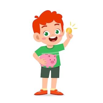 Милый маленький мальчик держит копилку и золотую монету Premium векторы
