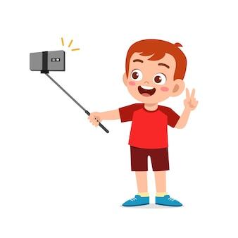 カメラの前でかわいい男の子のポーズと自分撮り