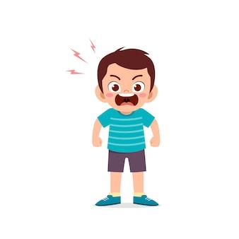Симпатичный маленький мальчик стоит и показывает выражение сердитой позы