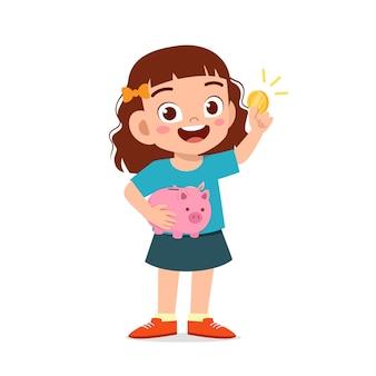 Милая маленькая девочка держит копилку и золотую монету