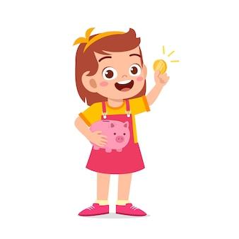 귀여운 꼬마 소녀는 돼지 저금통과 황금 동전을 들고